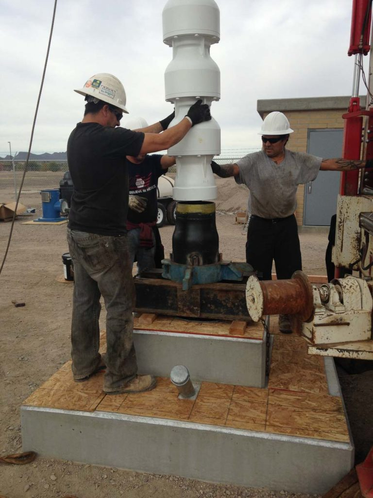 Group of men getting ready to drill a water well