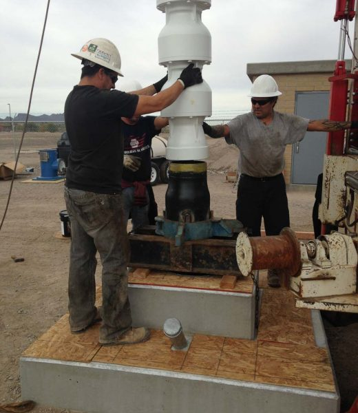 Group of men setting up well drilling machine